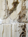 Open quarry of white marble sheer wall an on the east coast sardinia orosei a worker with the mask is intent on cutting the Stock Image