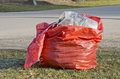 Open red plastic rubbish bag sack in park spring city Royalty Free Stock Photography