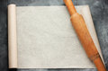 Open roll of baking parchment paper with rolling pin for menu or Royalty Free Stock Photo