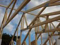 Open Roof Rafter Construction with Sky and Clouds