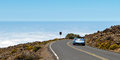 Open roofed car cruising down towards the clouds and the pacific ocean in the distance on the steep road to and from the ft high Stock Photos