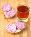 Open sandwich with sausage and hot tea in the glass tumbler Stock Photo