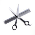 Open scissors on a gray comb isolated Royalty Free Stock Photo
