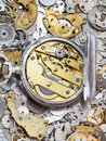 Open silver pocket watch on pile of spare parts Royalty Free Stock Photo