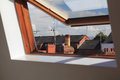 Open skylight or velux window showing the roof tops of terraced houses on a sunny day Stock Photos