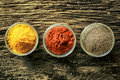 Open spice containers overhead view of three with colourful curry chilli powder or red pepper on an old aged weathered wooden Stock Photography