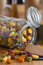 Open Storage Jar with colorful Pasta and Cooking Spoon Royalty Free Stock Images