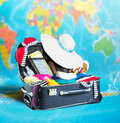 Open suitcase full of clothing on map Stock Photo