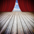Open theater red curtains and wooden floor against a cloudy sky Royalty Free Stock Photo