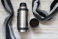 Open thermos flask and scarf on a woden background. Top view Royalty Free Stock Photo
