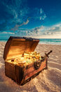 Open treasure chest on the beach with shinny gold Royalty Free Stock Image