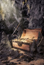Open treasure chest with bright gold in a cave Stock Photos