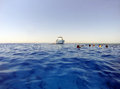Open water and divers with boat swimmers in the clear blue tropical sea the white yacht red sea egypt Royalty Free Stock Photography