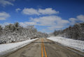 Open winter road through the trees during the with a big sky and clouds Stock Photography