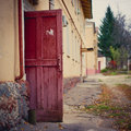 Open wooden door of a dilapidated building close up an painted in dark red in autumn Royalty Free Stock Photos
