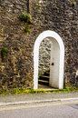 Open wooden door with pointed gothic arch on a white stone wall Royalty Free Stock Photo