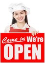 We are open a young woman wearing chef s hat holding a store opening signboard Royalty Free Stock Image