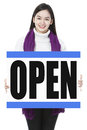 We are open a young woman in winter clothes holding a store opening signboard Royalty Free Stock Image