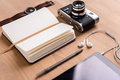 Opened blank notebook, old camera, tablet,  earphones, watch and pen Royalty Free Stock Photo