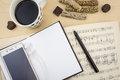 Opened blank notebook with smartphone, cup of coffee and music notation book