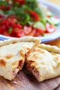Opened calzone close up closed italian pizza on the wood table Royalty Free Stock Images
