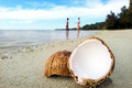 Opened coconut on sandy beach with couple bathing in the water of a deserted island in aitutaki lagoon cook island Royalty Free Stock Photography