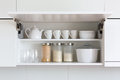 Opened cupboard with kitchenware inside white Royalty Free Stock Photography