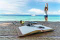 Opened empty notepad is on the table with sunglasses, phone, headphones at the background of tropical sea and relaxing Royalty Free Stock Photo