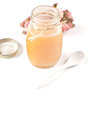 Opened jar of honey with spoon and copy space isolated Royalty Free Stock Image