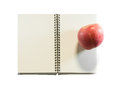 Opened note book with apple Royalty Free Stock Photo