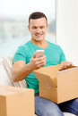 Opening cardboard box and taking out smartphone post home technology lifestyle concept smiling man with in it Royalty Free Stock Photos