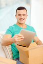 Opening cardboard box and taking out tablet pc post home technology lifestyle concept smiling man with computer in it Royalty Free Stock Image