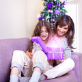 Opening christmas present young brunette mother with teen girl excited faces magical glowing light from gift box happiness and Stock Image