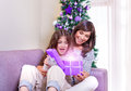Opening christmastime gift excited mother with daughter sitting at home near beautiful decorated christmas tree enjoying magical Stock Photos