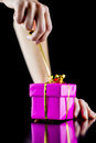 Opening a gift box closeup of female hand pink wrapped over black background Stock Image