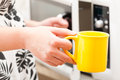 Opening the microwave oven with mug in other hand Stock Photos