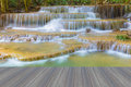 Opening wooden floor close up beautiful blue stream water falls in deep national park Royalty Free Stock Images