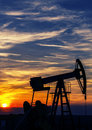 Operating oil and gas well contour outlined on sunset sky at in active european play Stock Photos