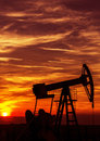 Operating oil and gas well contour outlined on sunset sky at in active european play Stock Images
