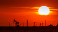 Operating oil and gas well contour outlined on sunset sky with bright solar disc at Stock Photo
