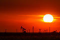 Operating oil and gas well contour outlined on sunset sky with bright solar disc at Stock Photos