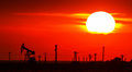 Operating oil and gas well contour outlined on sunset sky with bright solar disc at Royalty Free Stock Photo