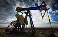 Operating oil well profiled on dramatic cloudy sky Royalty Free Stock Photos