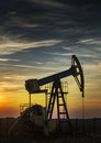 Operating oil well profiled on sunset sky dramatic Stock Image
