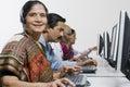 Operatore femminile di servizio di assistenza al cliente in sari with colleagues in office Fotografia Stock
