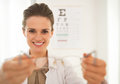 Ophthalmologist doctor woman giving eyeglasses smiling in front of snellen chart Royalty Free Stock Photo