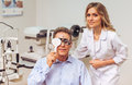 At the ophthalmologist handsome middle aged men on consultation covering one eye and checking visual acuity young beautiful female Stock Photos
