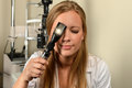 Ophthalmologist Looking through Ophthalmoscope Royalty Free Stock Image