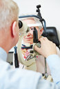 Ophthalmologist using slit lamp to check eye of senior woman Stock Photography