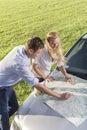 Opinião de ângulo alto do mapa da leitura dos pares na capa do carro durante a viagem por estrada Fotografia de Stock